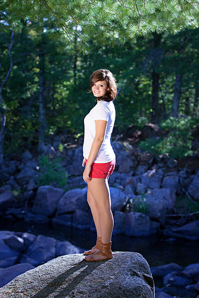 Natural Light Senior Photo shoot in woods standing on rock red shorts white top